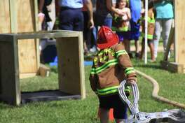 Kids get to wear firefighter gear during the Friendswood Volunteer Fire Department and EMS Open House on Oct. 7.