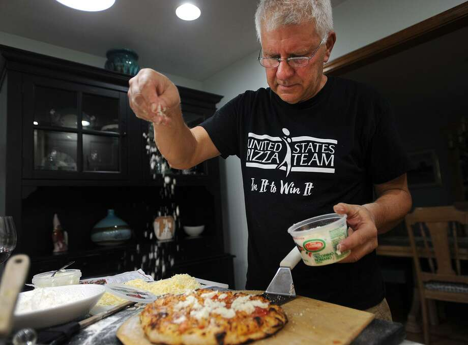 Dave Conti, of Seymour, sprinkles some romano cheese on his lobster fra diavolo pizza that took first place honors at the United States Pizza Cup in Oceanside, Calif. in August. Conti will represent the United States at the pizza world championships in Parma, Italy in April of next year. Photo: Brian A. Pounds / Hearst Connecticut Media / Connecticut Post