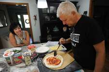As his wife, Kathy, looks on, Dave Conti sauces the dough.
