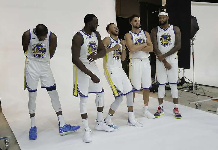 Golden State Warriors' Kevin Durant, from left, Draymond Green, Stephen Curry, Klay Thompson and DeMarcus Cousins wait to pose for photos for the team's photographer during media day at the NBA basketball team's practice facility in Oakland, Calif., Monday, Sept. 24, 2018. (AP Photo/Jeff Chiu)
