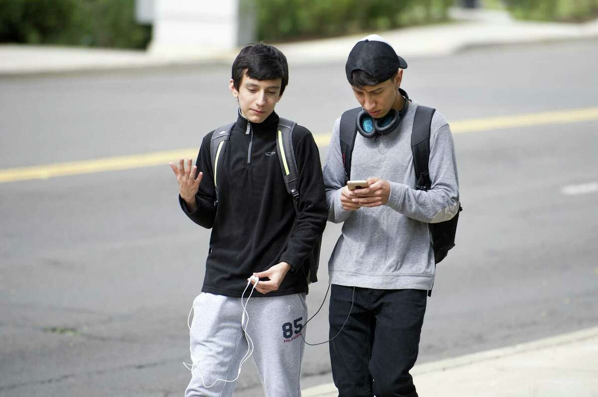 A student looks down at his cellphone while walking past Stamford High School in Stamford.