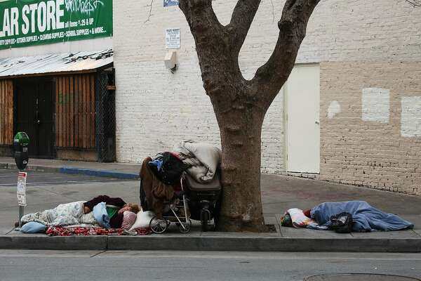 FILE -- Homeless people sleep on a sidewalk at Larkin Street near City Hall in San Francisco, May 9, 2016. A federal appeals court ruled that laws punishing homeless people for sleeping in public violate the constitution. (Jim Wilson/The New York Times)