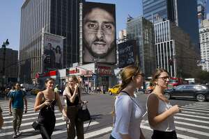 FILE - In this Sept. 6, 2018, file photo, people in New York walk past a Nike advertisement featuring former San Francisco 49ers quarterback Colin Kaepernick, known for kneeling during the national anthem to protest police brutality and racial inequality. How is Nike's new ad featuring former NFL quarterback Colin Kaepernick affecting the company's sales? Investors will be listening for what the athletic apparel company has to say on the subject Tuesday, Sept. 18, when Nike serves up its latest quarterly results. (AP Photo/Mark Lennihan, File)
