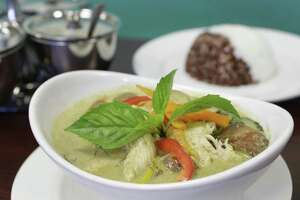 A dish of green curry with brown and steamed rice is shown at Aim Thai Restaurant, 9734 W Montgomery Rd., Friday, April 21, 2017, in Houston. ( Melissa Phillip / Houston Chronicle )