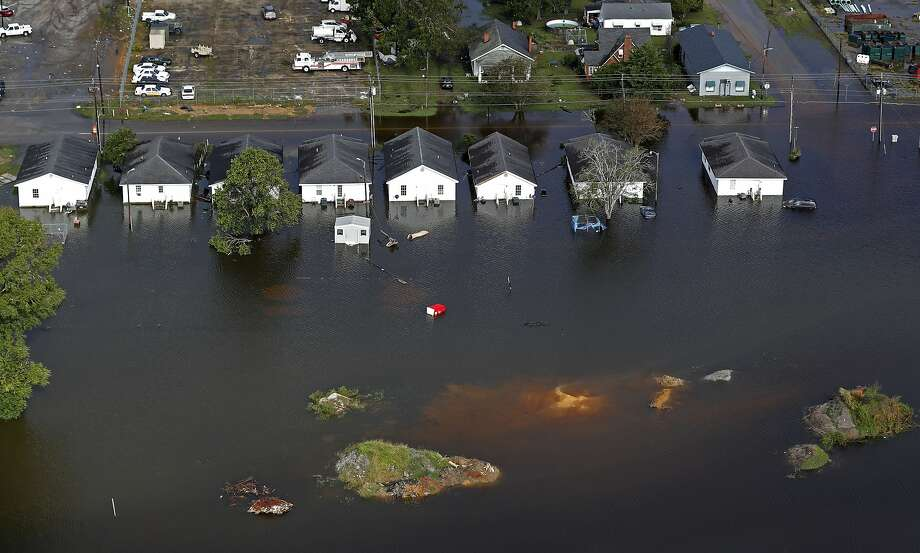 In this Monday, Sept. 17, 2018, file photo, floodwaters from Hurricane Florence surround homes in Dillon, S.C. Scientists say climate change likely boosted rainfall totals for both Florence and 2017's Harvey. (AP Photo/Gerald Herbert) Photo: Gerald Herbert / Associated Press