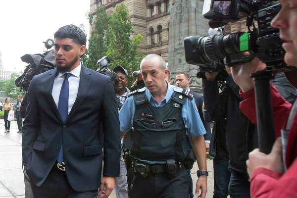 Houston Astros' Roberto Osuna, left, leaves a Toronto court on Tuesday, September 25, 2018. The former Toronto Blue Jays pitcher agreed to a peace bond that led to the withdrawal of an assault charge against him. He was charged in May with assault in a domestic violence case. (Chris Young/The Canadian Press via AP)