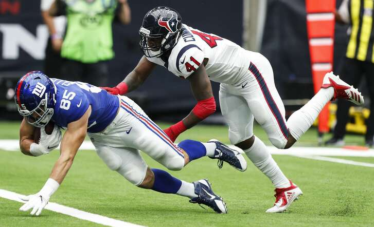 New York Giants tight end Rhett Ellison (85) dives past Houston Texans linebacker Zach Cunningham (41) into the end zone for a 16-yard touchdown reception during the second quarter of an NFL football game at NRG Stadium on Sunday, Sept. 23, 2018, in Houston.