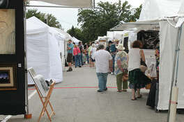 Visitors to the Edwardsville Art Fair browse the works on Friday evening, the first day of the three-day event.