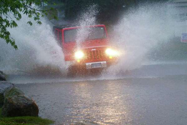 Motor vehicles attempt to drive through a flooded East Rocks Road at St. Mary's Tuesday, September 25, 2018, in Norwalk, Conn. Heavy rains prompted flash flood warning for the area.
