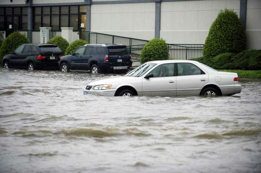 A car sits after being abandoned due to rising flood waters at the intersection of Jefferson Ave. and Harborview Ave. in south Stamford, Conn. on Tuesday, Sept. 25, 2018.