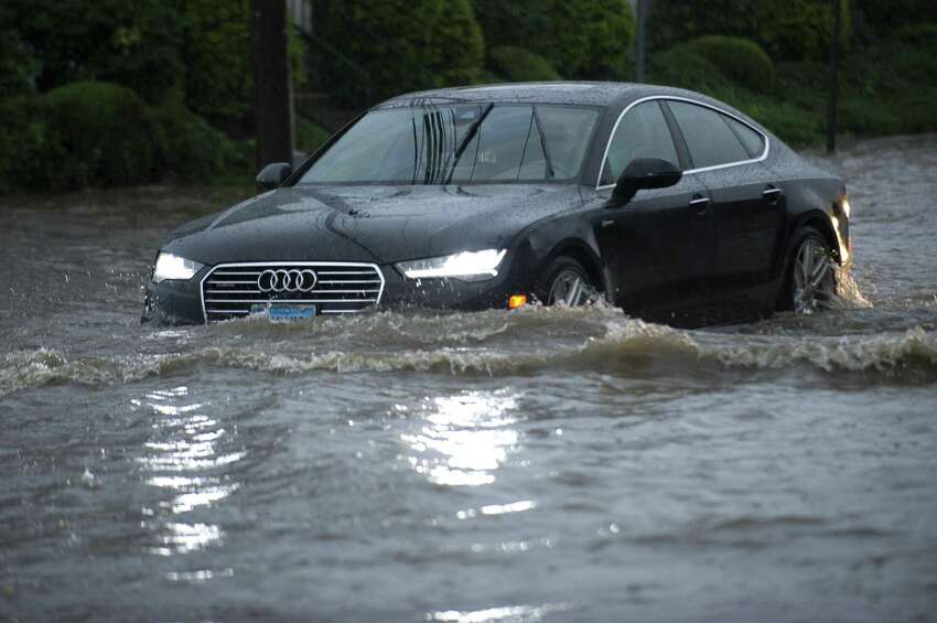 Cars slowly move through the flooded intersection of Jefferson Ave. and Harborview Ave. in south Stamford, Conn. on Tuesday, Sept. 25, 2018.