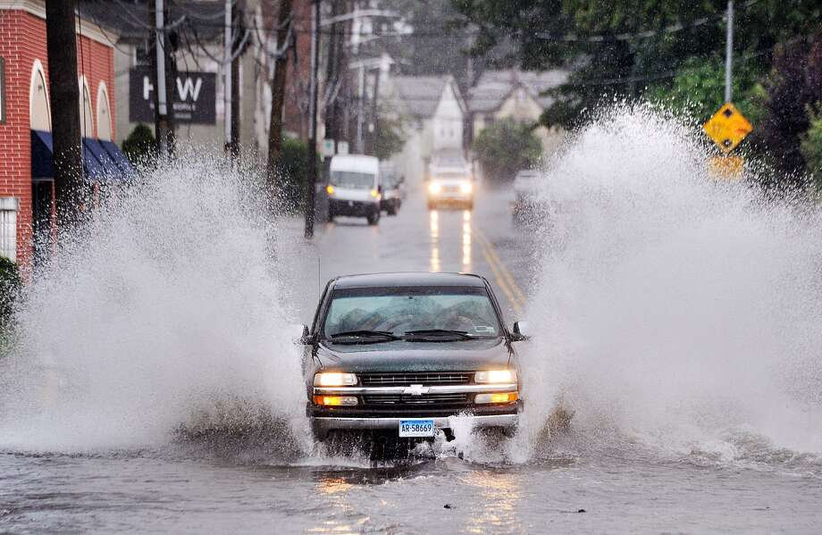 A vehicle with a Connecticut license plate sprays water while traveling through a flooded North Main Street in Port Chester, N.Y., as it crosses the state border into Greenwich, Conn., Tuesday, Sept. 25, 2018. Heavy rainfall during the day caused flooding on roadways throughout both states. Photo: Bob Luckey Jr. / Hearst Connecticut Media / Greenwich Time