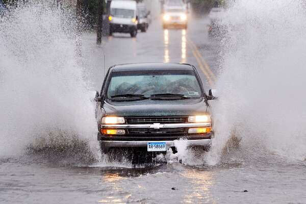 A vehicle with a Connecticut license plate sprays water while traveling through a flooded North Main Street in Port Chester, N.Y., as it crosses the state border into Greenwich, Conn., Tuesday, Sept. 25, 2018. Heavy rainfall during the day caused flooding on roadways throughout both states.