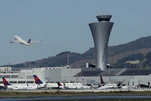 FILE - In this Oct. 24, 2107 file photo, the air traffic control tower is in sight as a plane takes off from San Francisco International Airport in San Francisco. Video captured the moment that an off-course Air Canada jet flew just a few dozen feet over the tops of four other jetliners filled with passengers. On Tuesday, Sept. 25, 2018, the National Transportation Safety Board will consider the probable cause of the close call at the airport. (AP Photo/Jeff Chiu, File)