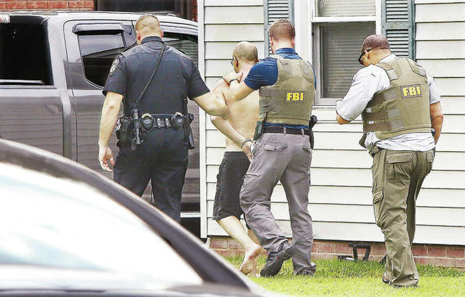 Agents from the Federal Bureau of Investigation, and an Alton police officer, escort a shirtless and shoeless man from the front of the house he was in, in handcuffs, Tuesday morning in the 3200 block of Agnes Blvd. in Alton. The man was taken to the back of the house while agents searched the interior for any other occupants. FBI agents, Alton police and Lt. David Vucich, the computer crimes expert for the Madison County Sheriff's Department, all gathered on a nearby shopping center parking lot about 8:30 a.m. to coordinate the apparent execution of a search warrant. Agents arrived ready to use a battering ram on the front door when the man, who was apparently the only occupant, answered the door. An Alton Fire Department ambulance was standing by on a nearby street as a precaution. Agents spent hours at the house photographing the exterior and interior of the home. An agent with the FBI returned a phone call from a Telegraph reporter, but was unable to divulge further details. Photo: John Badman | The Telegraph