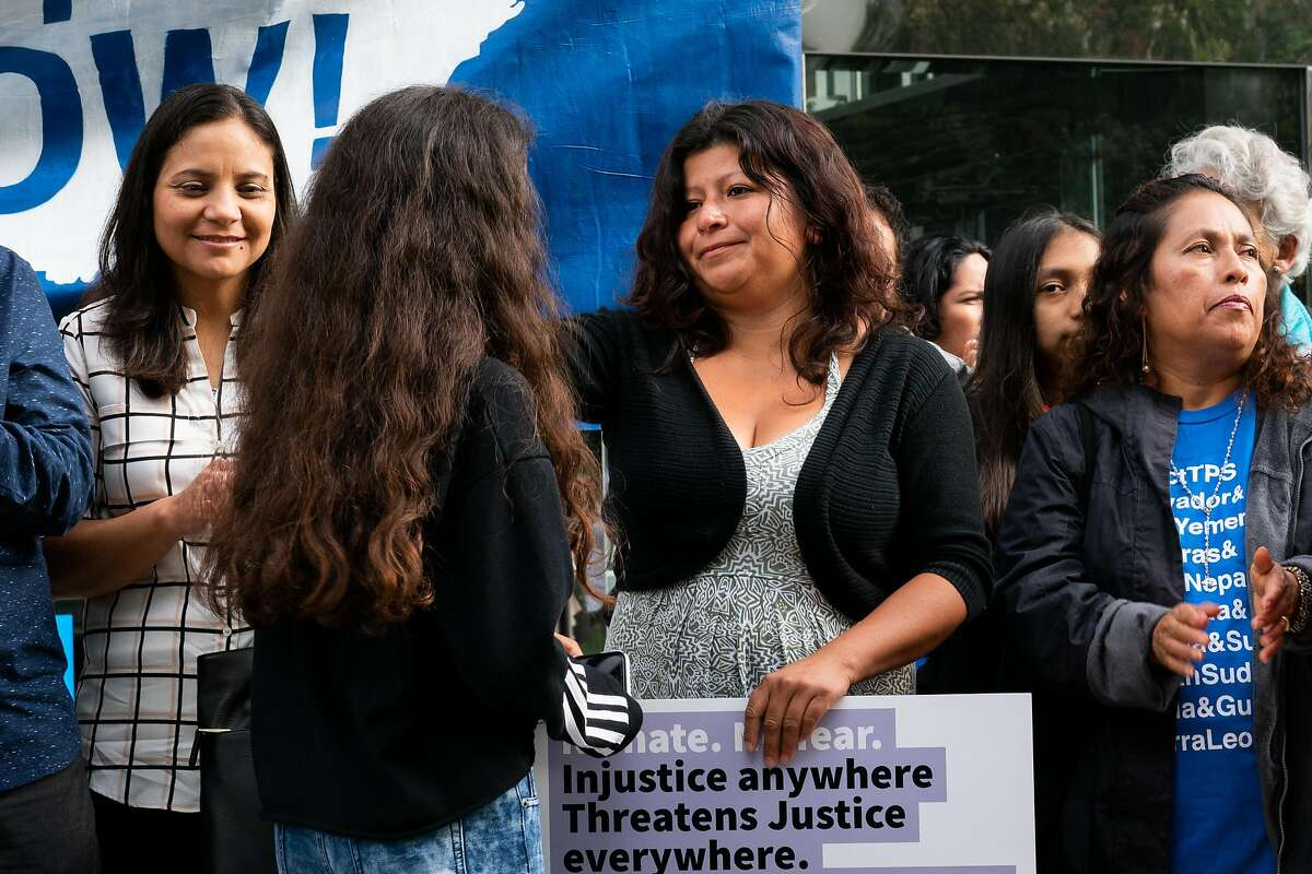 Cristina Morales (center) smiles at her daugher, Crista Ramos, 14, the lead plaintiff in the Ramos v. Neilsen lawsuit, during a press conference requesting temporary injunction of the Trump administration's decision to end Temporary Protected Status (TPS) for people from four countries, including Sudan, Nicaragua, Haiti and El Salvador at Phillip Burton Federal Building in San Francisco on Tuesday, September 25, 2018.