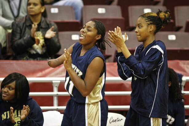Nimitz senior, Jesse Landry, 11, (left) cheers along with teammate Taylor McGee (right) during the Nimitz vs. Aldine girls high school basketball game at the MO Campbell Center Friday, Jan. 14, 2011, in Houston. Landry has played a key role for her team this season, not held down by opponents or her handicap. ( Michael Paulsen / Houston Chronicle )