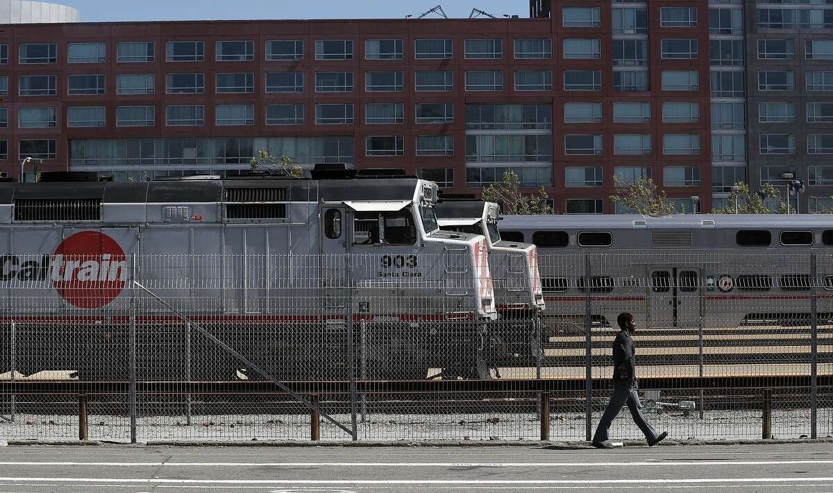 A man walks by stopped trains at the Caltrain rail station in San Francisco, Calif., on Sunday, April 22, 2018. A new report for a planned rail extension into downtown would now eliminate the need to demolish the I-280 extension, as previously proposed.