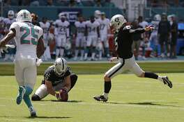 Oakland Raiders kicker Mike Nugent (6) boots a field goal as punter Johnny Townsend (5) holds while being rushed by Miami Dolphins cornerback Xavien Howard (25) during the first half of an NFL football game, Sunday, Sept. 23, 2018, in Miami Gardens, Fla. (AP Photo/Lynne Sladky)