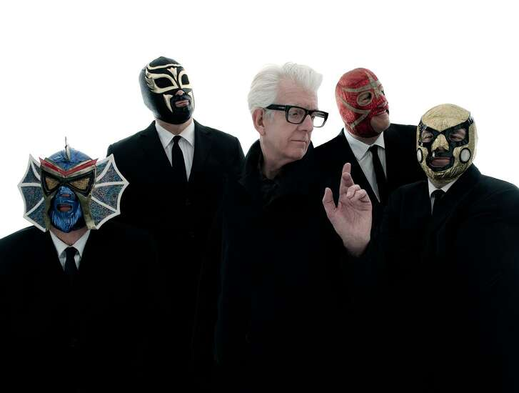 Singer and songwriter Nick Lowe pictured with rockabilly band Los Straightjackets.