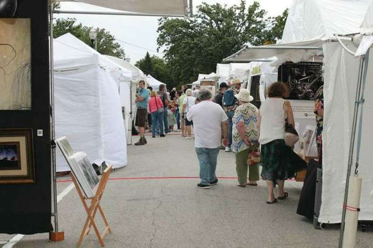 """Visitors of the Edwardsville Art Fair browse the artists' works on Friday evening, the first day of the three-day event last weekend. Melissa McDonough-Borden, executive director of the Edwardsville Arts Center, said the event was a """"giant success."""""""