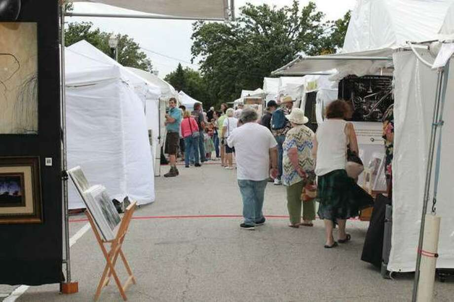 "Visitors of the Edwardsville Art Fair browse the artists' works on Friday evening, the first day of the three-day event last weekend. Melissa McDonough-Borden, executive director of the Edwardsville Arts Center, said the event was a ""giant success."" Photo: Bill Tucker 