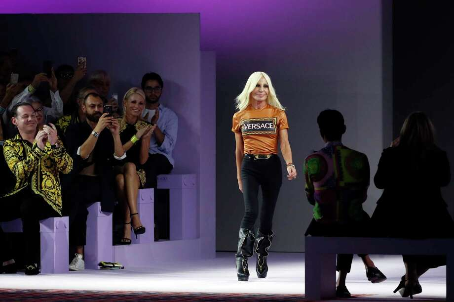 FILE - In this Sept. 21, 2018, file photo, Donatella Versace comes on the catwalk at the end of Versace's women's 2019 Spring-Summer collection, unveiled during the Fashion Week in Milan, Italy. Michael Kors is buying the Italian fashion house Gianni Versace in a deal worth more than $2 billion in a hard  charge into the world of high end fashion. The deal announced Tuesday, Sept. 25, follows the New York handbag maker's $1.35 billion acquisition last year of the high-end shoemaker Jimmy Choo. (AP Photo/Antonio Calanni, File) Photo: Antonio Calanni / Copyright 2018 The Associated Press. All rights reserved.