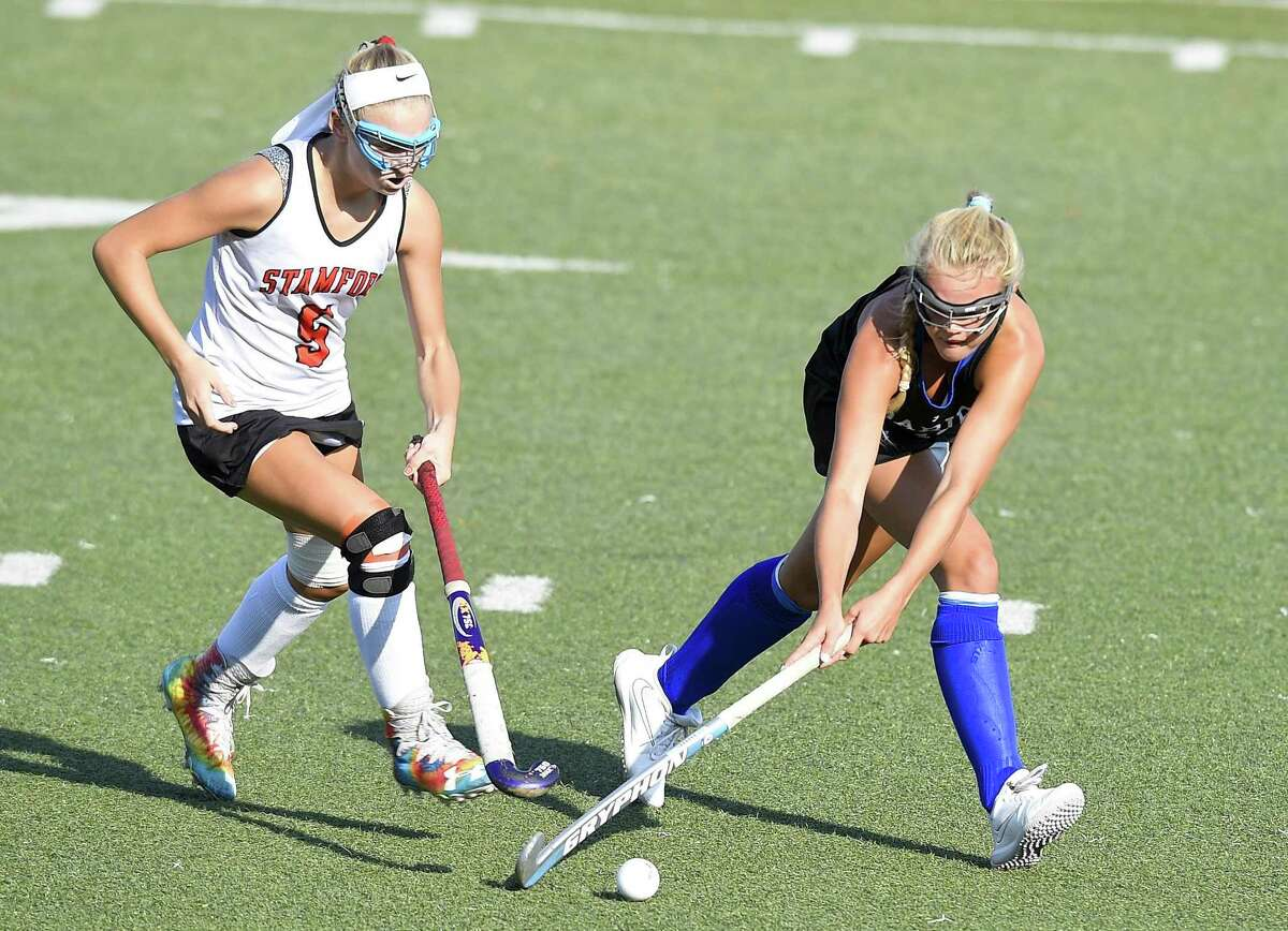 Darien's Teddy Maloney, right, drives midfield against Stamford's Kaity Young on Sept. 20.
