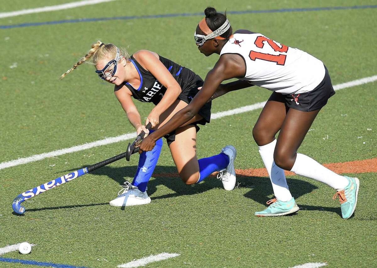 Darien's Izzy Smith, left, passes off the ball under pressure from Stamford's Tamia James in an FCIAC contest on Sept. 20.