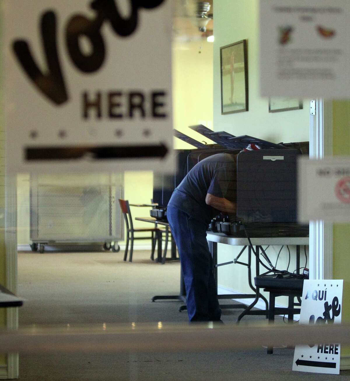 A man leans into a voting booth at the Olmos Basin Golf Course in San Antonio.