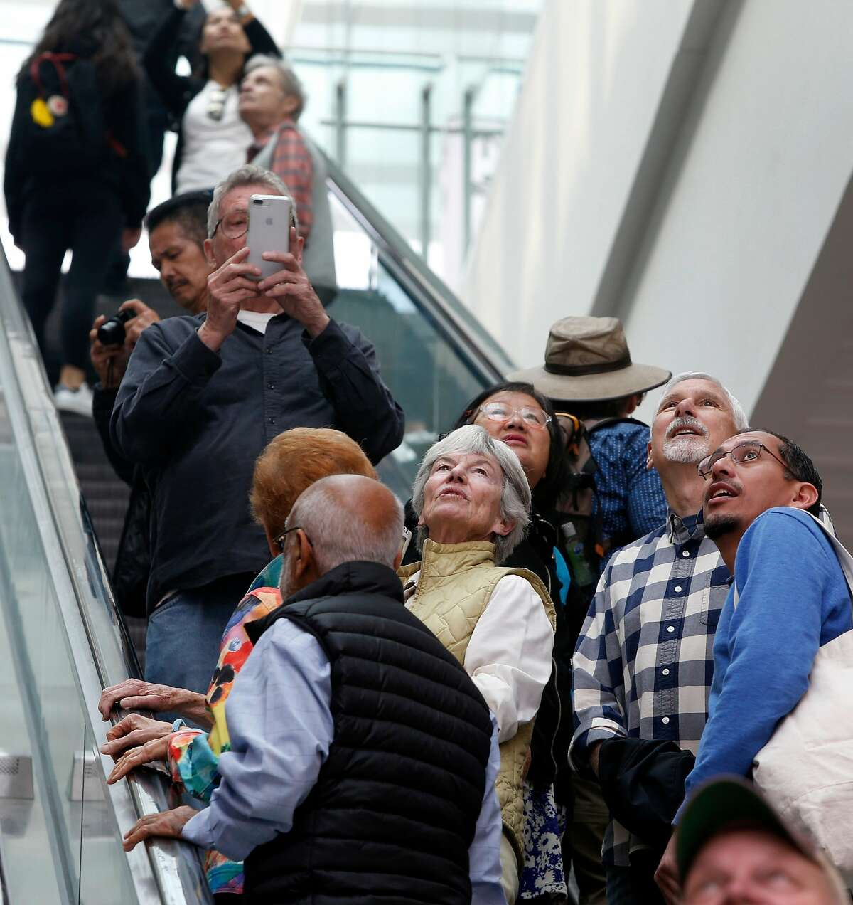 Visitors attending the grand opening of the Salesforce Transit Center gaze up at the oculus while ascending an escalator to the bus deck level in San Francisco, Calif. on Saturday, Aug. 11, 2018. Buses begin rolling through the terminal Sunday.
