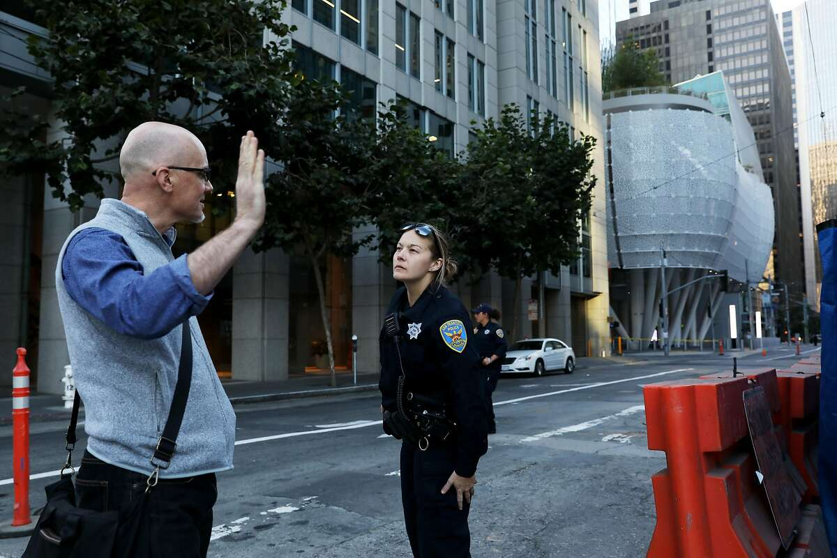 San Francisco police officer K. Larkey talks to a pedestrian after the closure of the SalesForce Transit Center in San Francisco, Calif., on Tuesday, September 25, 2018.