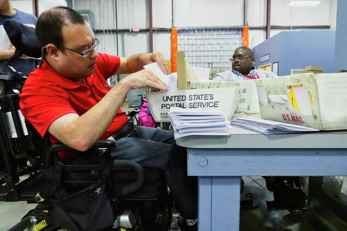 Rich Whaley, a clerk at the Center for Disability Services mail fulfillment center in Colonie, works on a job at the center in this Times Union file photo. Roughly 20 employees there are losing their jobs after the cancelation of a state contract. (Paul Buckowski/Times Union)