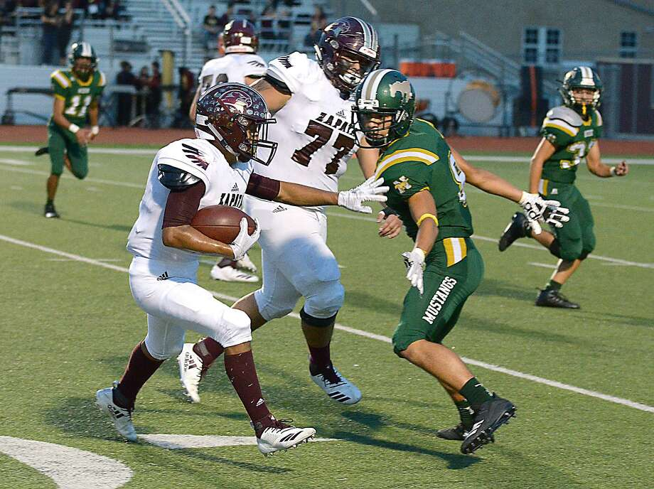 Xavi Rodriguez carries the ball for the Zapata Hawks as Hector Rogerio defends for the Nixon Mustangs, Friday, September 21, 2018 at Shirley Field. David Tamguma Jr., blocks for the Hawks. Photo: Cuate Santos /Laredo Morning Times / Laredo Morning Times