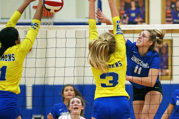 Madison Glassco takes a shot for the Unicorns over Kimira Coffee (left) and Ashley Breu as Clemens hosts New Braunfels in volleyball on September 25, 2018.