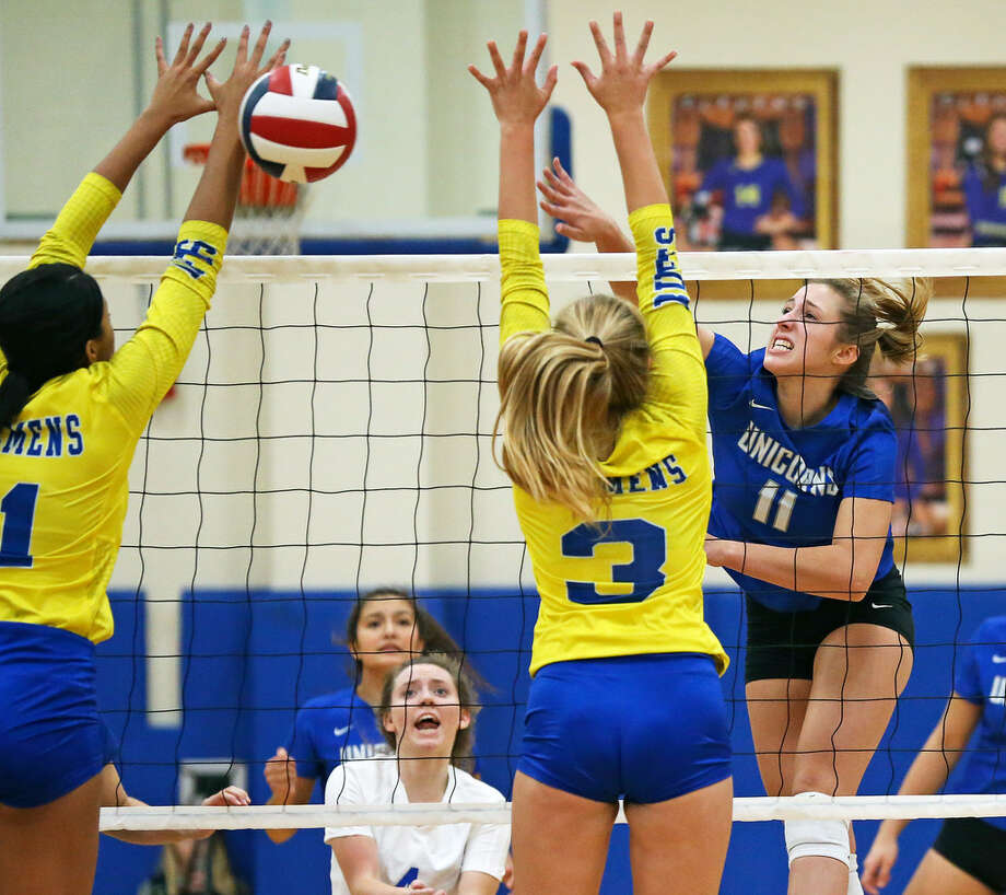 Madison Glassco takes a shot for the Unicorns over Kimira Coffee (left) and Ashley Breu as Clemens hosts New Braunfels in volleyball on September 25, 2018. Photo: Tom Reel