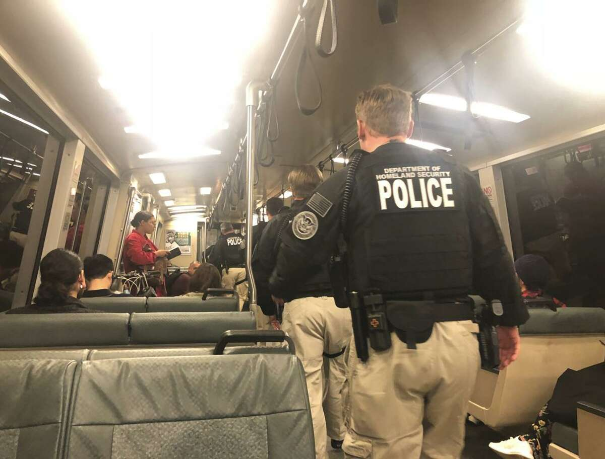 At least eight armed, uniformed DHS officials walk in the aisle among seated passengers on a BART train bound for the Civic Center BART station in San Francisco on Tuesday, Sept. 25, 2018.