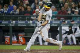 Oakland Athletics' Matt Olson connects on a ground-rule double to score Nick Martini during the sixth inning of a baseball game against the Seattle Mariners on Tuesday, Sept. 25, 2018, in Seattle. (AP Photo/Jennifer Buchanan)