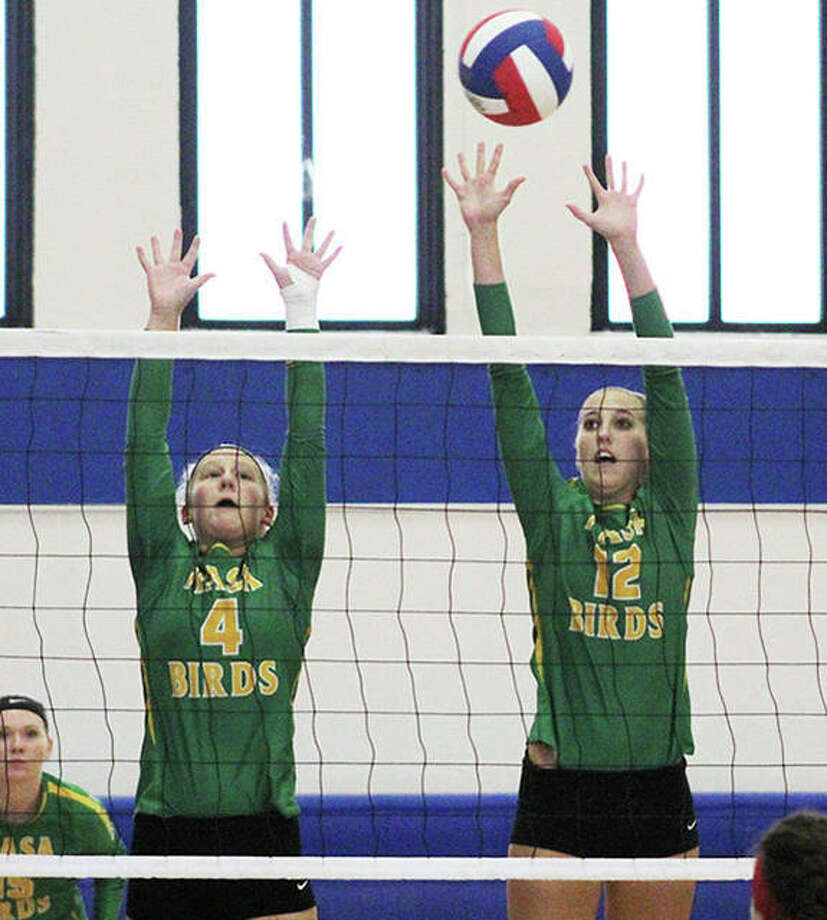 Southwestern's Bri Roloff (left) and Lexy Hall, shown putting up a block in a match earlier this season at the Roxana Tournament, were back at home Tuesday night and defeated Brussels in three sets to extend their unbeaten streak to six matches in a row. Photo: Greg Shashack / The Telegraph
