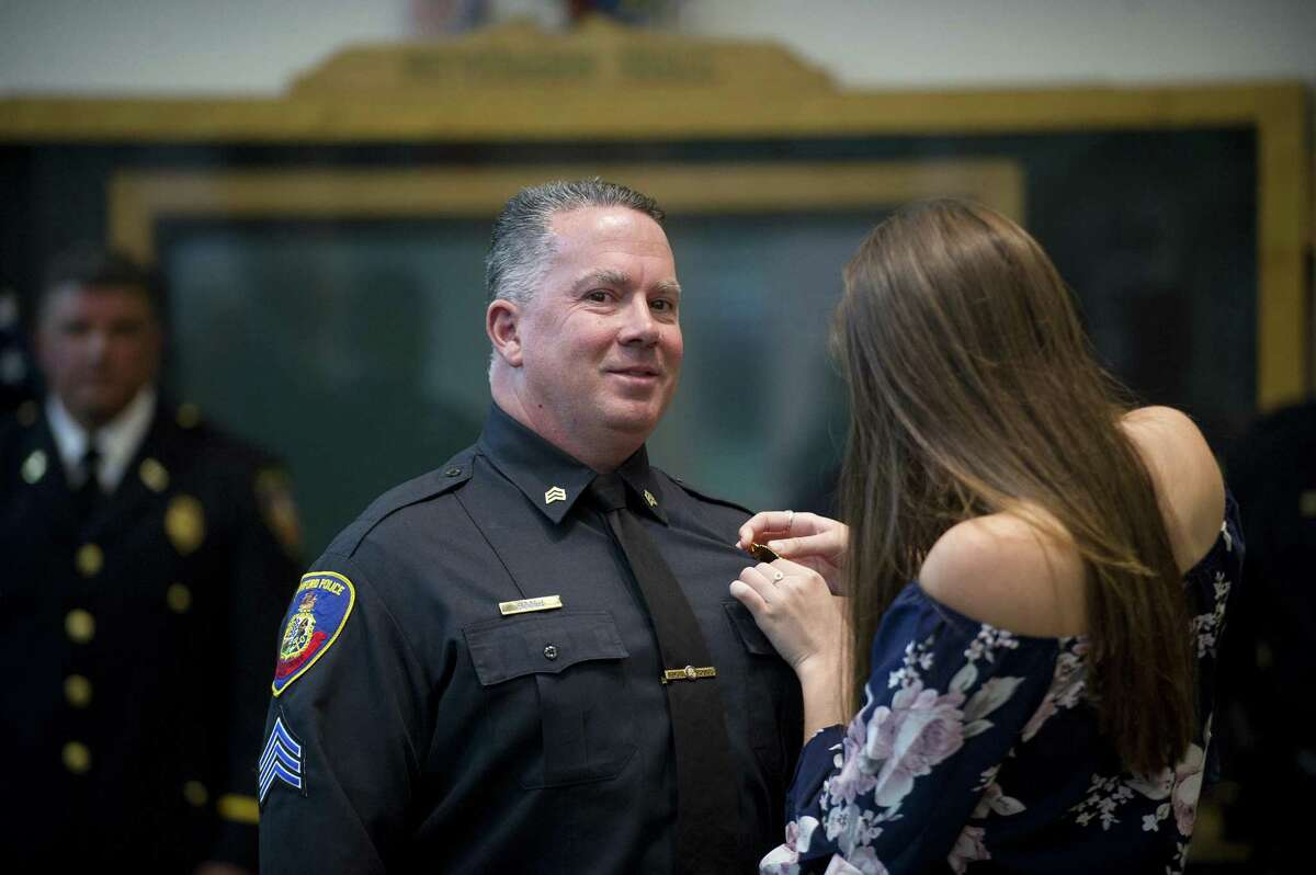 Sergeant Jeffrey Booth has a new badge pinned to his uniform by his daughter Emily Booth, 18, during the police promotion ceremony inside Government Center in downtown Stamford, Conn. on Tuesday, Sept. 25, 2018.