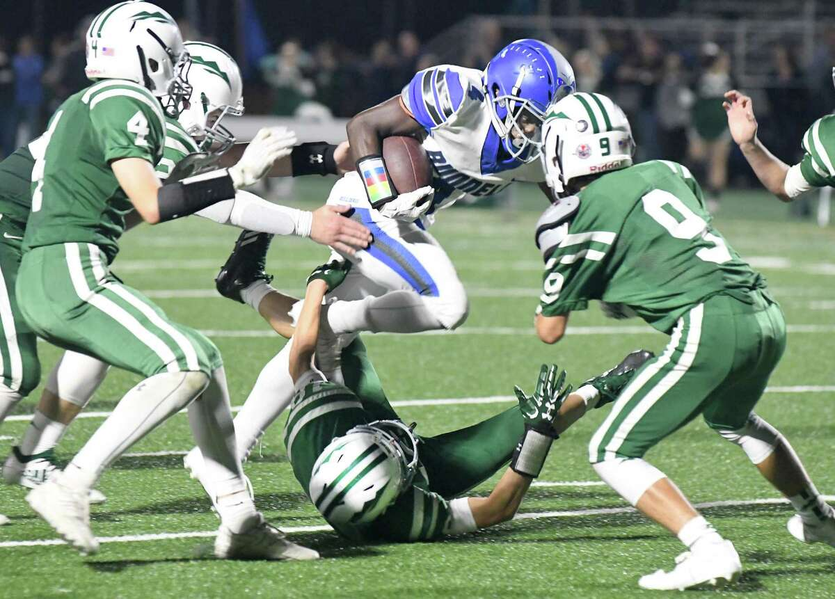 New Milford players from left, Connor Gannon, Ian Magner, Kyle Beebe (on ground), and Michael Muller try to stop Bunnell's Christ N'Dabian at New Milford High School on Friday. Bunnell won 41-3.