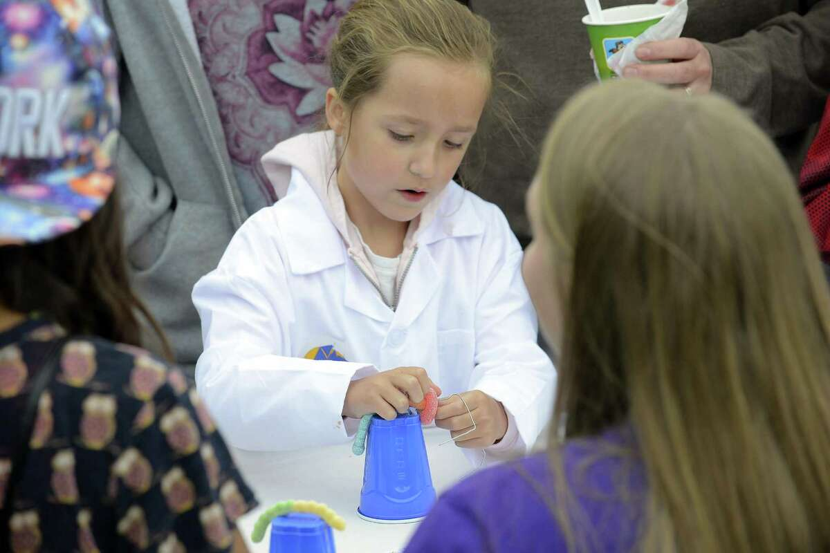 In this file photo, Emily Brandt attempts to put a gummy ring around a gummy worm without using her hands at STEMFest in Mill River Park. This Sunday, the free, daylong festival will feature hands-on science, technology, engineering and math activities for all ages.
