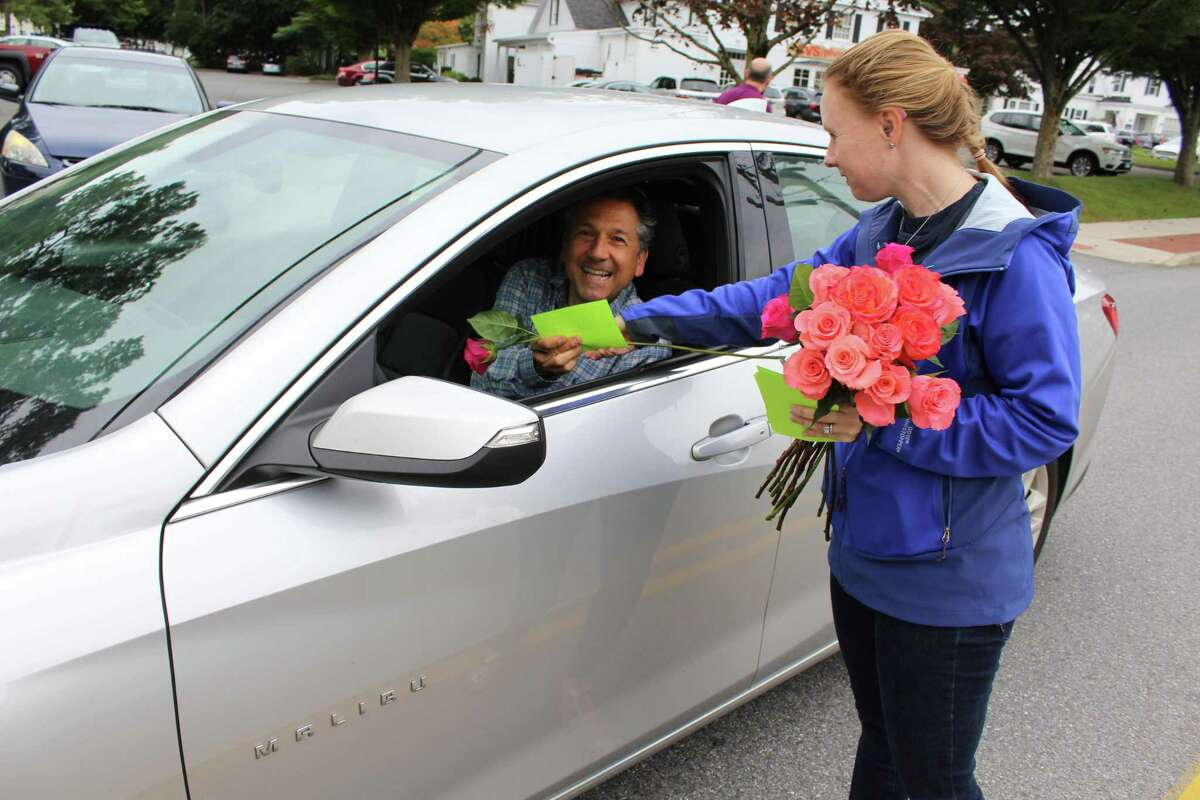 """Rachel Nelson, a member of Our Lady of Fatima in Wilton, hands a stranger a rose as a part of the Wilton Chamber of Commerce's """"Random Acts of Kindness"""" day on Friday, Sept. 21, 2018."""