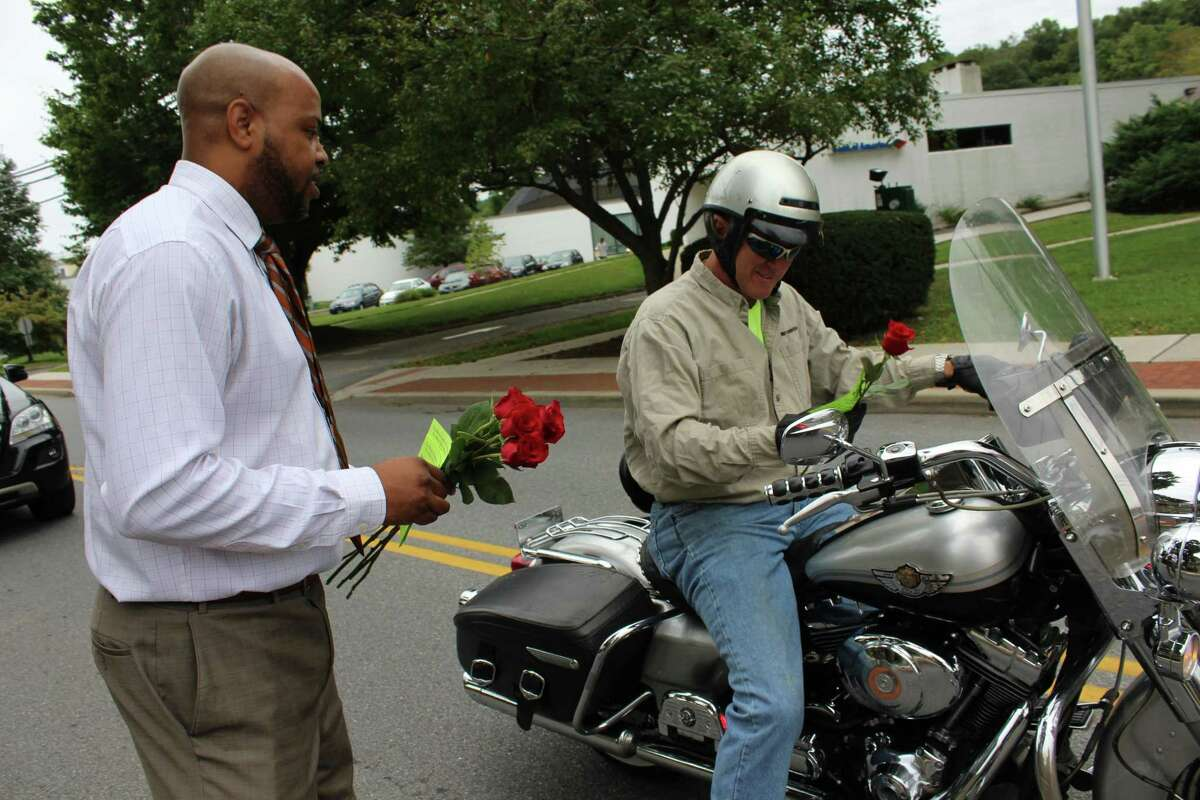 """Michael Smith, a member of the Wilton Chamber of Commerce, hands a stranger a rose as a part of the chamber's """"Random Acts of Kindness"""" day on Friday, Sept. 21, 2018."""