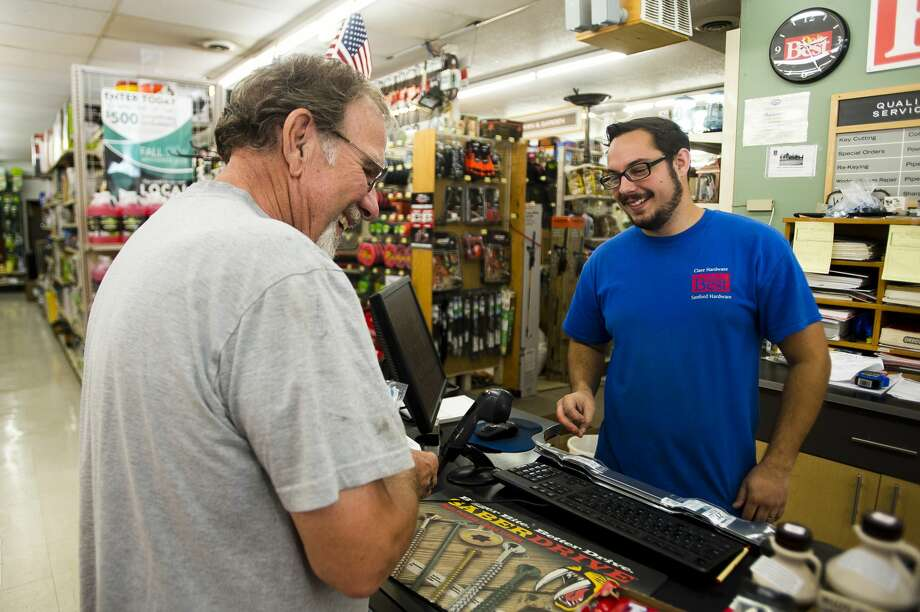Sanford Hardware employee Ryan Keyes, right, chats with John Durfee, left, after Durfee made a purchase inside the store on Wednesday, Sept. 26, 2018. (Katy Kildee/kkildee@mdn.net) Photo: (Katy Kildee/kkildee@mdn.net)
