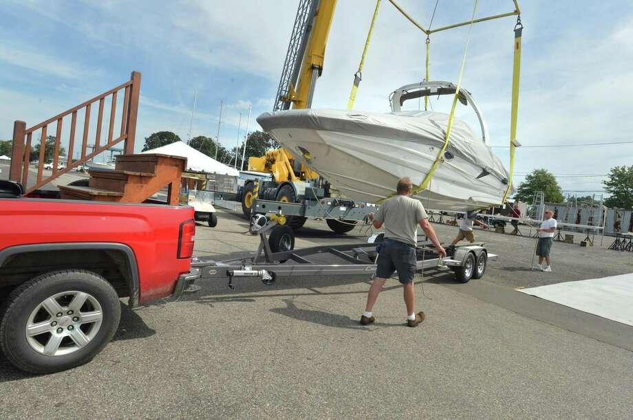 Norwalk Cove Marina workers move a vessel in September 2018 at the Norwalk Boat Show in Norwalk, Conn. Photo: Alex Von Kleydorff / Hearst Connecticut Media / Norwalk Hour