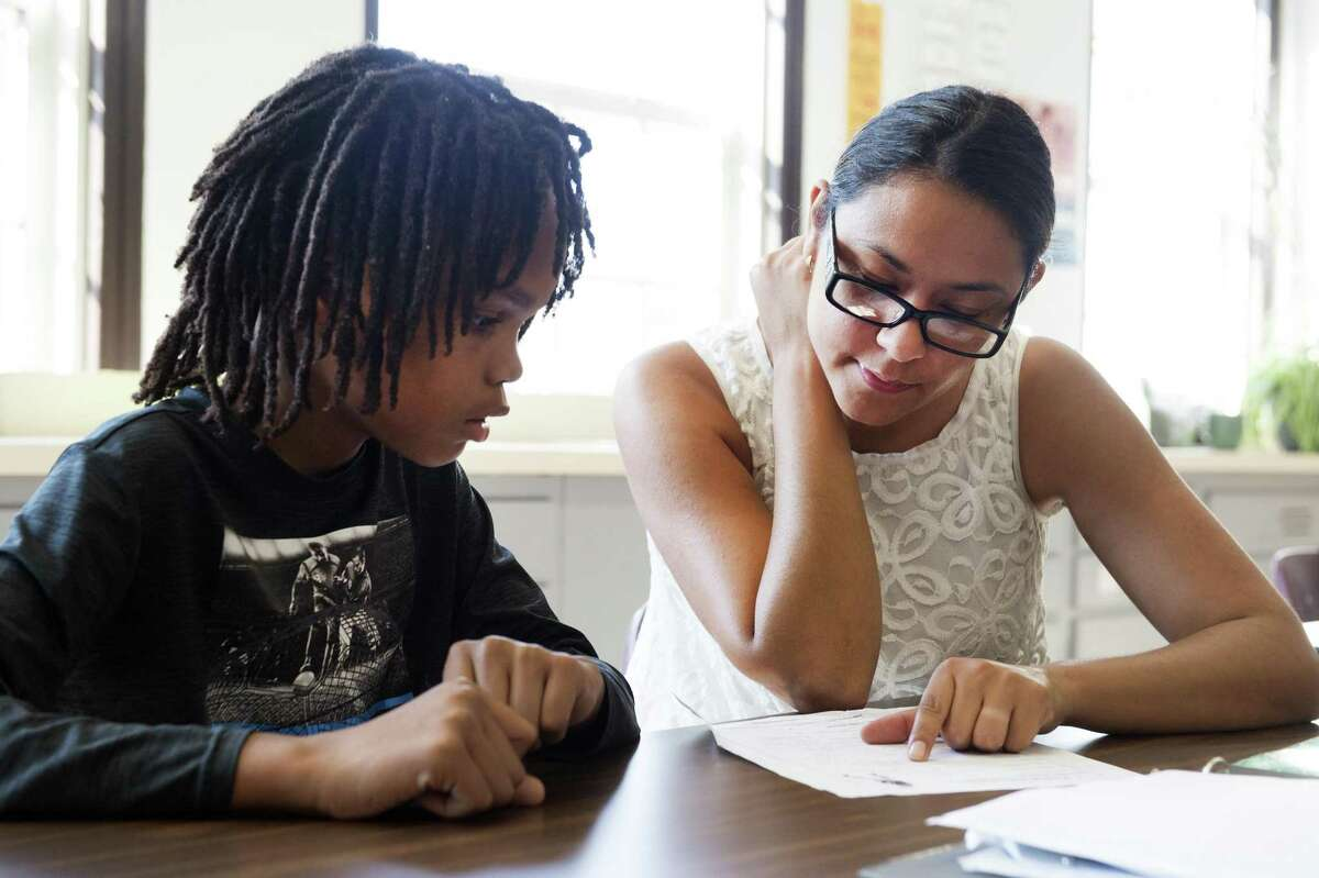 FCA staff member Daisy Velez helps a student with his homework during the ASPIRE after-school program.