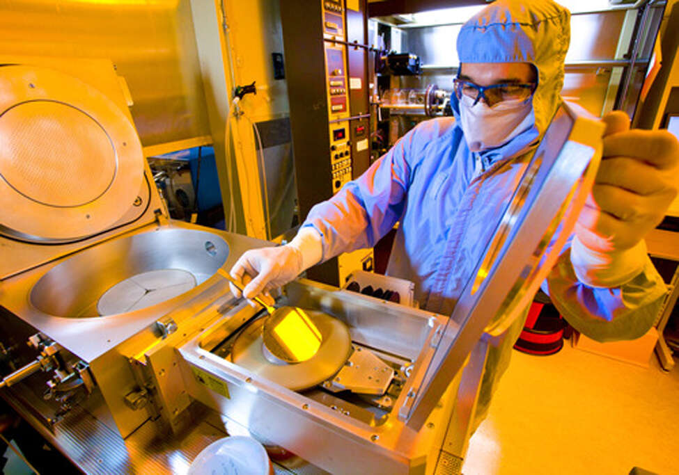 A GE worker with silicon carbide wafers at the company's research lab in Niskayuna. GE is transferring its silicon carbide chip development to SUNY Poly in Albany.