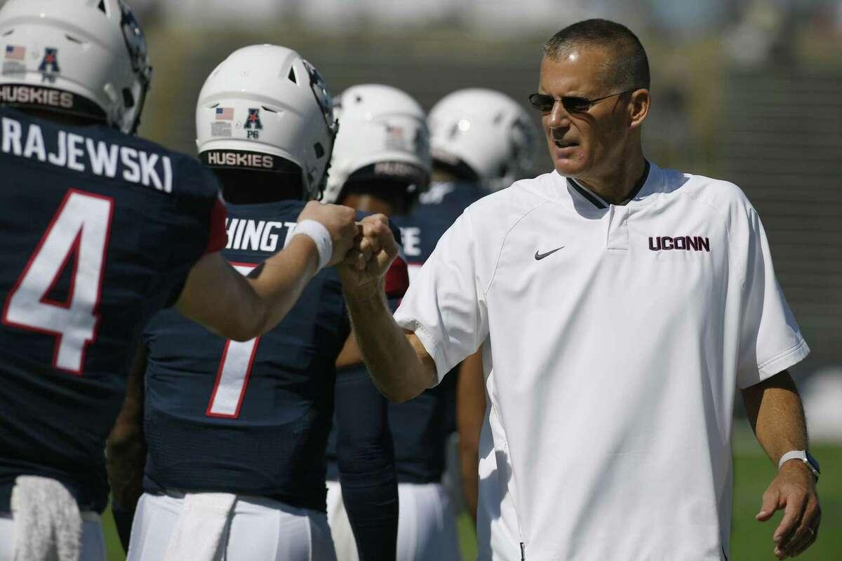 UConn head coach Randy Edsall bumps fists with quarterback Steven Krajewski during a game on Sept. 15.