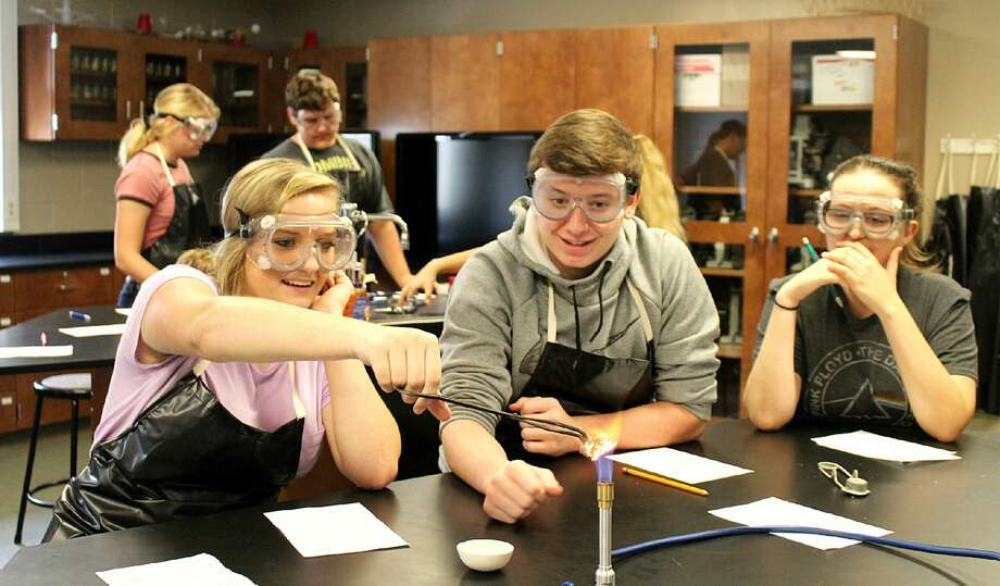 (From left) Laker High students Savannah Beachy, Jax McCabe and Ava Ceci recently conducted a chemistry experiment, in which they had to examine whether the mass of a piece of steel wool increases or decreases after burning it. Students discovered that the mass of the steel wool increases because oxygen in the fire oxidizes and rusts the iron. The experiment was led by teacher Deb Hasselschwert. Photo: Courtesy Photo